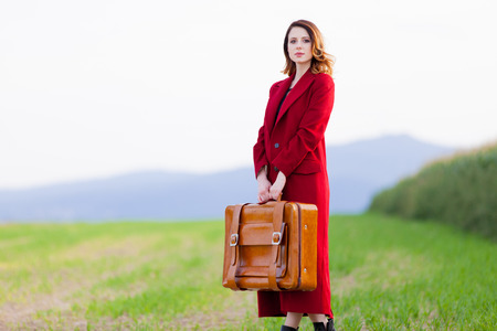 Portrait of young woman in red coar at autumn countryside with suitcase. photo