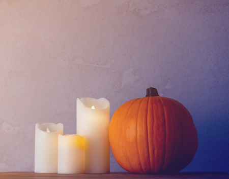 Orange Autumn pumpkin and candles on wooden table near grey wall at background