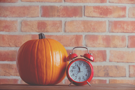 Autumn pumpkin and alarm clock on wooden table with brick wall at background