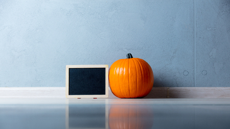Orange Autumn pumpkin with menu blackboard on floor near grey wall at background