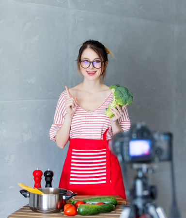 Young caucasian blogger woman cooking Vegan food at camera for Video-sharing website. Home location at kitchen Stock Photo