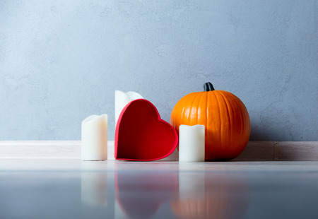 Orange Autumn pumpkin and candles with heart shape box on floor near grey wall at background
