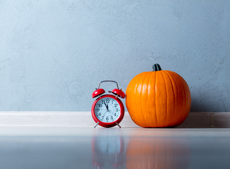 Orange Autumn pumpkin with red alarm clock on floor near grey wall at background
