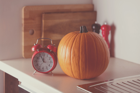 Beautiful Autumn pumpkin and retro alarm clock on a table in kitchen
