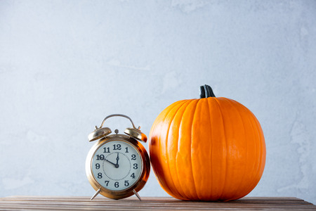 Fresh Autumn pumpkin and retro alarm clock on wooden table near grey wall at background