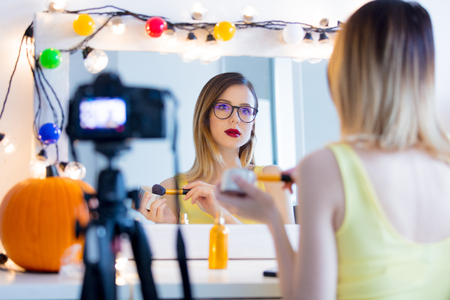 Young caucasian blogger woman applying cosmetics at camera for Video-sharing website. Home location near a mirror