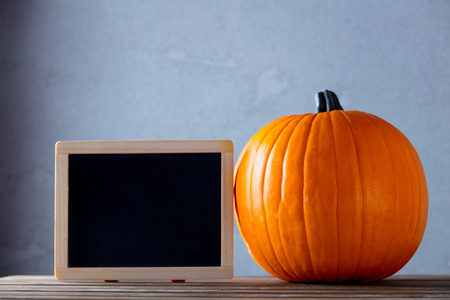 Fresh Autumn pumpkin and blackboard menu on wooden table near grey wall at background Stock Photo