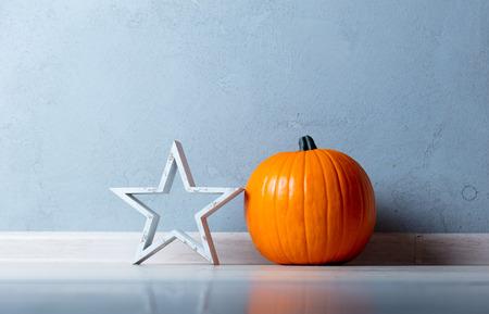 Orange Autumn pumpkin and docoration shape star on floor near grey wall at background Stock Photo
