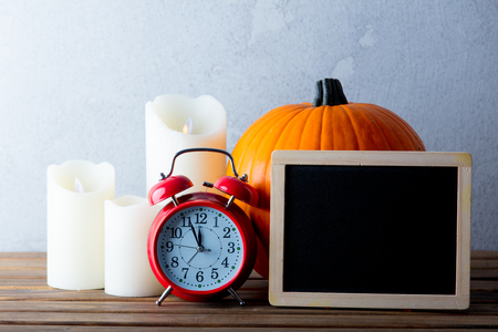 Fresh Autumn pumpkin and candles with menu blackboard and alarm clock on wooden table near grey wall at background