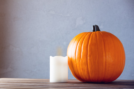 Fresh Autumn pumpkin and candle on wooden table near grey wall at background Stock Photo