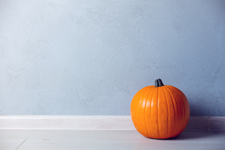 Orange Autumn pumpkin on floor near grey wall at background