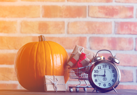 Autumn pumpkin and alarm clock with shopping cart full of gifts on wooden table with brick wall at background