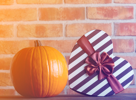Autumn pumpkin and heart shape gift box on wooden table with brick wall at background