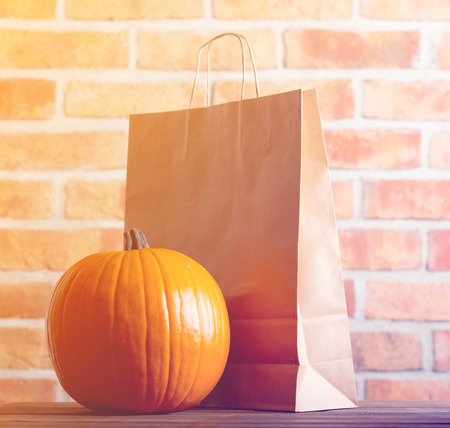Autumn pumpkin and eco package on wooden table with brick wall at background