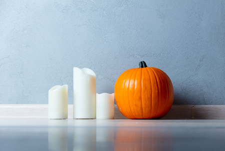 Orange Autumn pumpkin and candles on floor near grey wall at background Stock Photo