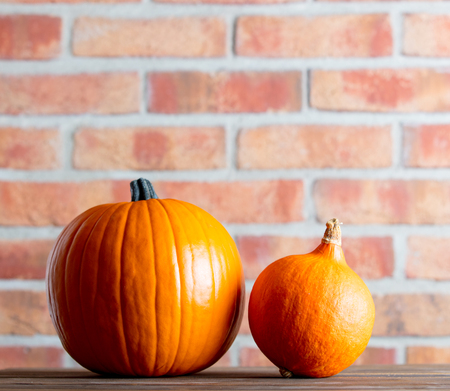 Two Autumn pumpkins on wooden table with brick wall at background