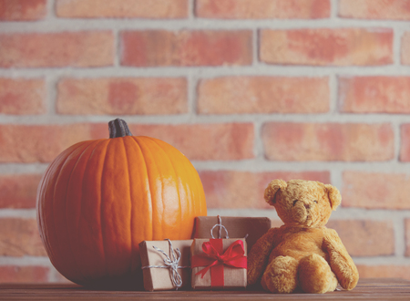 Autumn pumpkin and Teddy Bear with gifts on wooden table with brick wall at background