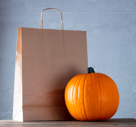 Fresh Autumn pumpkin and ECO shopping package on wooden table near grey wall at background