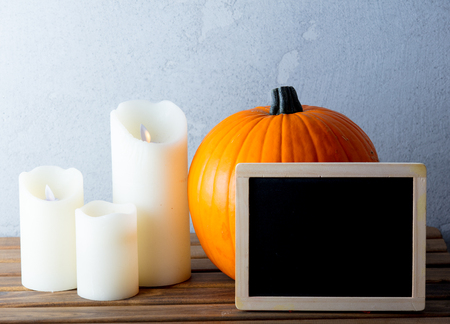 Fresh Autumn pumpkin and candles with menu blackboard on wooden table near grey wall at background