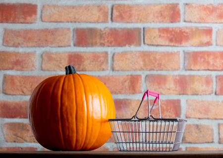 Autumn pumpkin and shopping basket on wooden table with brick wall at background