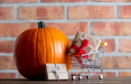 Autumn pumpkin and shopping cart with gifts on wooden table with brick wall at background Stock Photo