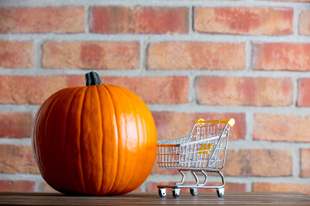 Autumn pumpkin and shopping cart on wooden table with brick wall at background