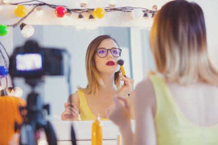 woman mirror: Young caucasian blogger woman applying cosmetics at camera for Video-sharing website. Home location near a mirror