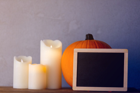 Orange Autumn pumpkin and candles with blackboard menu on wooden table near grey wall at background