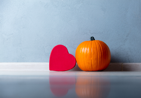 Orange Autumn pumpkin and heart shape box on floor near grey wall at background