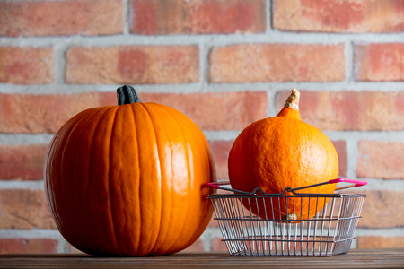 Two Autumn pumpkins and shopping basket on wooden table with brick wall at background
