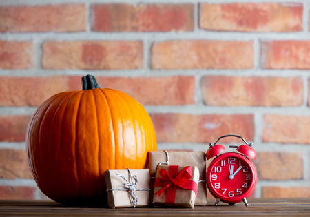 Autumn pumpkin and alarm clock with gifts on wooden table with brick wall at background Stock Photo