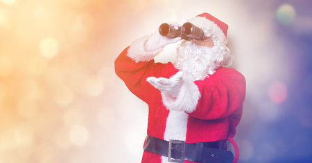 Funny Santa Claus holding binoculars on yellow background