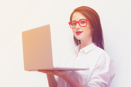 beautiful young woman with laptop standing in front of the wonderful blue background Stock Photo
