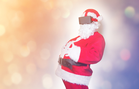 3 year old: Funny Santa Claus have a joy with VR glasses on yellow background