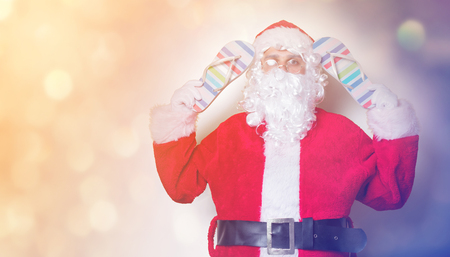 Funny Santa Claus holding flip flops on yellow background Stock Photo