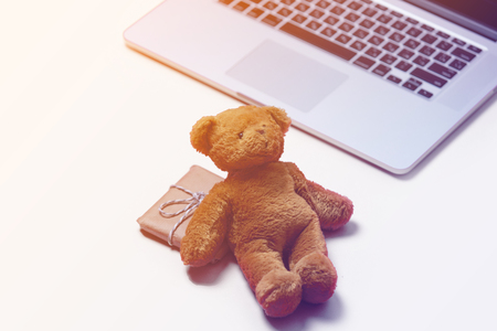 silver screen: beautiful small gift, cute teddy bear and cool laptop on the wonderful pink background