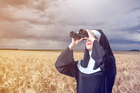 sotana: Young smiling nun with binoculars looking for something on wheat field background