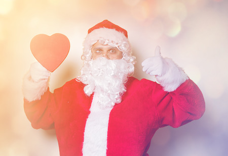 Funny Santa Claus have a joy and holding heart shape gift on yellow background