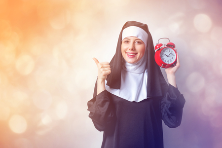 Young smiling nun with red alarm clock on white background Stock Photo