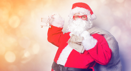 Funny Santa Claus have a fun with shopping cart on blue background Stock Photo