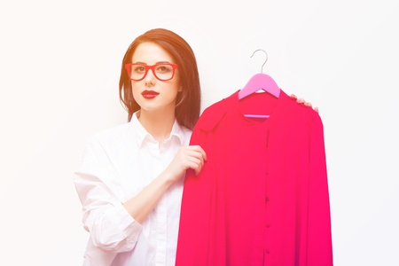 beautiful young woman with shirt on hanger standing in front of the wonderful blue background