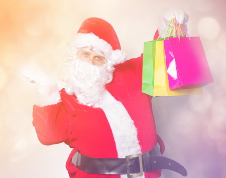 Funny Santa Claus have a fun with shopping bags on blue background Stock Photo