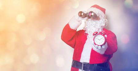 Funny Santa Claus holding binoculars and alarm clock on yellow background