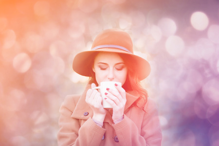 Woman with cup of tea or coffee at outdoor in autumn time