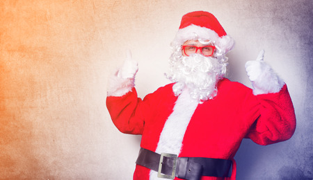 Funny Santa Claus have a fun with red eyeglasses on blue background Stock Photo
