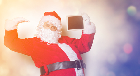 Funny Santa Claus holding black board on yellow background