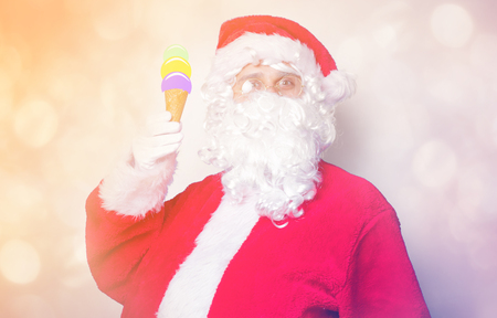 Funny Santa Claus have a fun with ice-cream on blue background