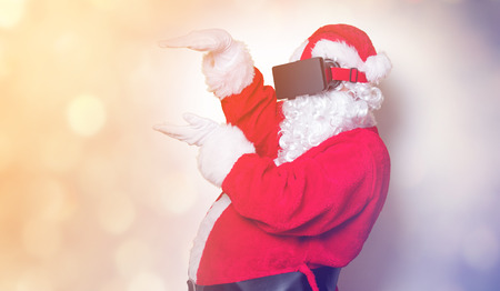 Funny Santa Claus have a joy with VR glasses on yellow background