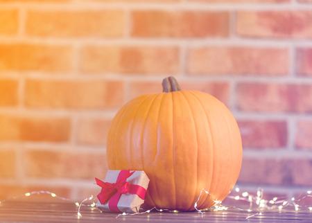 Autumn pumpkin with Fairy Lights at Halloween holiday on brick background Stock Photo