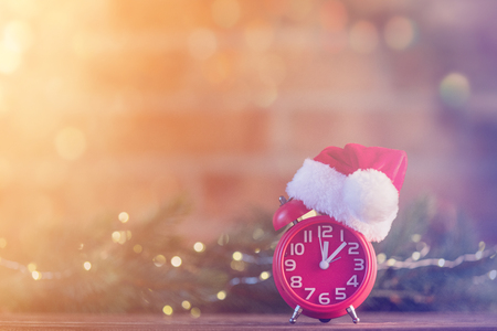 boxing day: Retro alarm clock with Santa Claus hat with Christmas Fairy Ligths and Pine tree at background Stock Photo